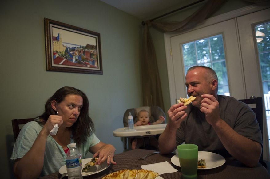 Joe Carr and his wife Sofia are joined by their kids Olivia, 8 months and Catalina, 5, as they sit down to home made pizza at their home in Downingtown, Pa., Friday, August 17, 2012. Mr. Carr and his wife Sofia were at one point unemployed at the same time. Sofia has returned to paralegal work and Joe has returned to work at the same construction company that laid him off recently. The home they own was a foreclosed property which they renovated and currently live in. (Rod Lamkey Jr./The Washington Times)