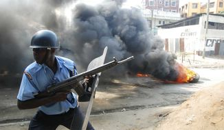 A riot police officer runs near a tire on fire, lit by Muslim youths, outside Masjid Musa Mosque, in Majengo, Mombasa, Kenya, Tuesday, Aug. 28, 2012. (AP Photo)