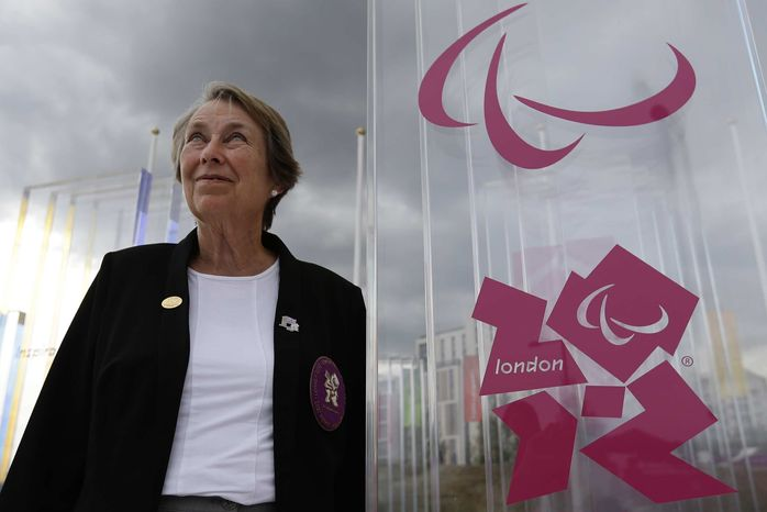 ** FILE ** In this Thursday, Aug. 23, 2012, photo, Eve Loeffler, daughter of the founder Paralympic games, Ludwig Guttman, stands by the logo of the Paralympic Games at the athletes village at the Paralympic park. (AP Photo/Alastair Grant)