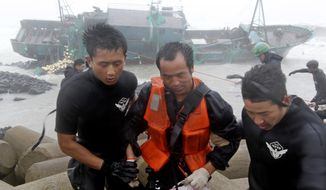 A Chinese fisherman (center) is rescued Aug. 28, 2012, by South Korean coast guard officers from a Chinese ship in Jeju, South Korea, after a powerful typhoon pounded the nation with strong winds and heavy rain. The coast guard battled rough seas in a race to rescue fishermen on two Chinese ships that slammed into rocks off the southern coast. (Associated Press)