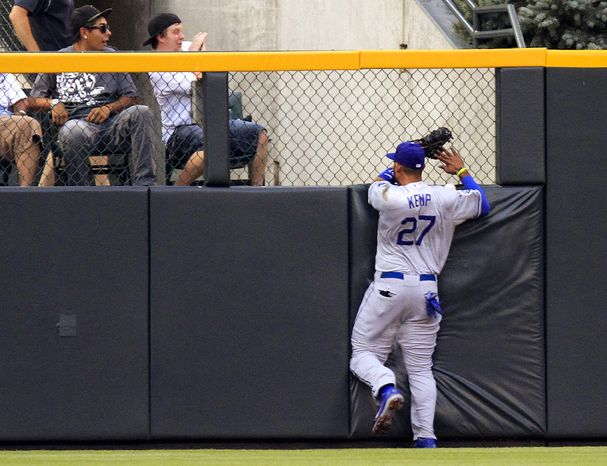 Los Angeles Dodgers center fielder Matt Kemp (27) slams into the wall chasing a Colorado Rockies' Josh Rutledge triple during the first inning of a baseball game, Tuesday, Aug. 28, 2012, in Denver. Kemp was injured on the play. (AP Photo/Barry Gutierrez)