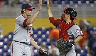 Washington Nationals relief pitcher Tyler Clippard, left, and catcher Kurt Suzuki celebrate after defeating the Miami Marlins 8-4 during a baseball game on Wednesday, Aug. 29, 2012, in Miami. (AP Photo/Wilfredo Lee)