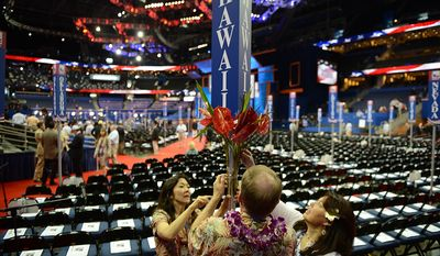 Alternate Delegate Sharin Burton, left, her husband Brad Burton, alternate Delegate and Delegate Janell Yim, all of Honolulu, Hawaii decorate the state placard marking their seats which, along with most Blue States, are among the furthest from the stage at the Republican National Convention at the Tampa Bay Times Forum in Tampa, Fla. on Wednesday, August 29, 2012. (Andrew Harnik/ The Washington Times)