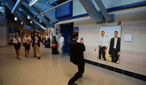 John Gio Karis, a Republican National Committee volunteer from Chicago, Ill., uses his phone to photograph a photo of Mitt Romney and Rep. Paul Ryan at the Republican National Convention at the Tampa Bay Times Forum in Tampa, Fla. on Wednesday, August 29, 2012. (Andrew Harnik/ The Washington Times)