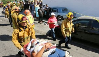 A Los Angeles City firefighter assists one of eight people injured when a car sped onto a sidewalk and plowed into a group of parents and children outside Main Street Elementary school, Wednesday Aug. 29, 2012 in Los Angeles. The crash occurred at 2:50 p.m., shortly after school had let out for the day, according to a statement from the Los Angeles Unified School District. Some of the people injured were children. (AP Photo/La Opinion, J. Emilio Flores)