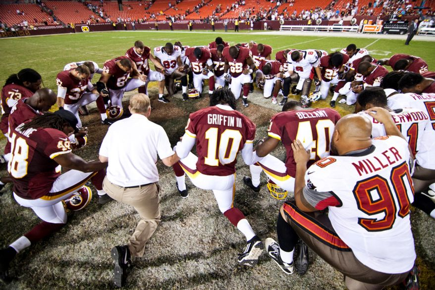 Washington Redskins quarterback Robert Griffin III (10) prays with players on both teams at center field at the end of the Tampa Bay Buccaneers at Washington Redskins preseason football game, Wednesday, August 29, 2012 in Washington, DC. (Craig Bisacre/The Washington Times)