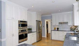 The kitchen features cork flooring, white cabinets and granite counters.