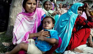 Hundreds of Christian families who fled their neighborhood where a girl was arrested on blasphemy charges sit in a public park for protection in Islamabad, Pakistan, on Tuesday. They feared retribution from Muslim neighbors if they stayed in their homes. (Associated Press)