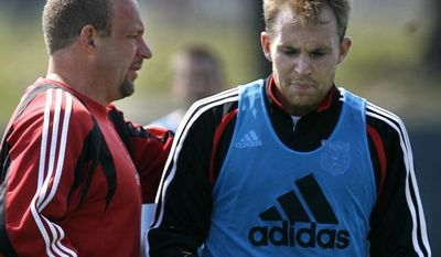 FILE - This March 22, 2007 file photo shows DC United head coach Thomas Soehn, left, talking with player Bryan Namoff at practice for the major league soccer team in Washington. Namoff has filed a $12 million lawsuit against the team and former coach Thomas Soehn, saying they rushed him back onto the field after the concussion that ultimately ended his career.  (AP Photo/Jacquelyn Martin, File)