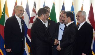 Iranian President Mahmoud Ahmadinejad (second right) welcomes Egyptian President Mohammed Morsi for the opening session of the Nonaligned Movement summit in Tehran on Aug. 30, 2012. (Associated Press/Iranian Presidency Office)