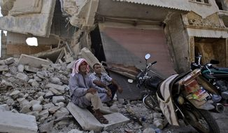 Syrian men rest on the rubble of a shop destroyed by Syrian government forces shelling on Aug. 30, 2012, while waiting their turn to buy bread from a bakery shop in the Syrian town of Azaz, on the outskirts of Aleppo. (Associated Press)