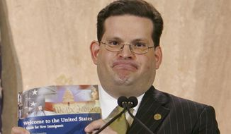 In this June 7, 2005 file photo, Alfonso Aguilar, head of Homeland Security's Office of Citizenship, displays a new guide, written for recently arrived legal residents. (AP Photo/Stefano Paltera) ** FILE **