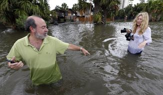 Kenny Melkin (left) helps his wife, Becky, navigate Aug. 31, 2012, through floodwaters from Hurricane Isaac as they make their way to see their flooded home in the West End Park neighborhood along Lake Pontchartrain in New Orleans. (Associated Press)