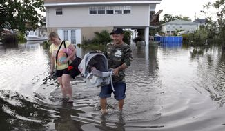 Tony Rodriguez (right) carries his baby daughter Nicole as he and his wife, Jodi Clelland, leave their flooded home in the aftermath of Hurricane Isaac in Slidell, La., on Aug. 31, 2012. Isaac is now a tropical depression and the center was on track to cross Arkansas on Friday and southern Missouri on Friday night, spreading rain as it goes. (Associated Press)