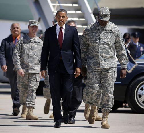 President Obama walks Aug. 31, 2012, on the tarmac upon his arrival at Biggs Airfield at Fort Bliss, Texas, with Gen. Lloyd Austin (right), vice chief of staff of the U.S. Army, to greet members of the military and their families. (Associated Press)