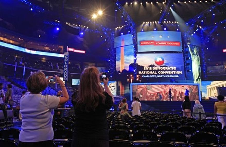 Visitors take photos of the main stage during the public unveiling of Democratic National Convention's facilities at Time Warner Arena in Charlotte, N.C., Friday, Aug. 31, 2012. (AP Photo/Chuck Burton)
