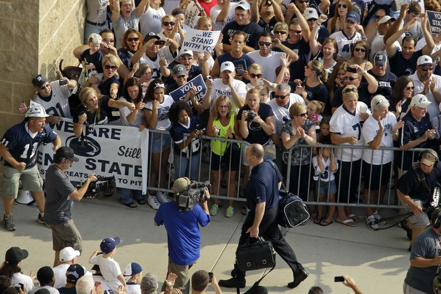 Penn State NCAA college football coach Bill O'Brien, right center foreground, leads his team into Beaver Stadium for their season opener against Ohio in State College, Pa., Saturday, Sept. 1, 2012. (AP Photo/Gene J. Puskar)