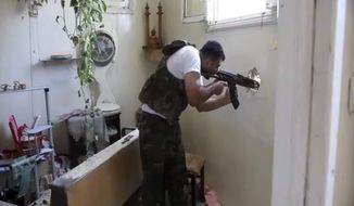 In this image made from video and accessed Saturday, Sept. 1, 2012, a Free Syrian Army fighter fires his weapon at a Syrian Army position through a hole in an empty and destroyed home during fighting in Aleppo, Syria. (AP Photo via AP video)