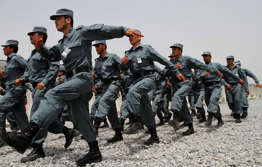 Newly graduated Afghan national police officers march during a graduation ceremony at a training center in Jalalabad, east of Kabul, Afghanistan, in 2011. The U.S. military has suspended training for at least a month while the process of vetting new Afghan recruits is reviewed. (Associated Press)