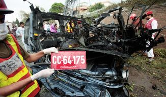 A Pakistani volunteer shows a number plate of the U.S. embassy vehicle hit by a blast in Peshawar, Pakistan on Monday, Sept. 3, 2012. A suicide bomber rammed a car filled with explosives into a U.S. government vehicle in northwestern Pakistan on Monday, killing two Pakistanis and wounding 19 others, including two Americans, officials said. (AP Photo/Mohammad Sajjad)
