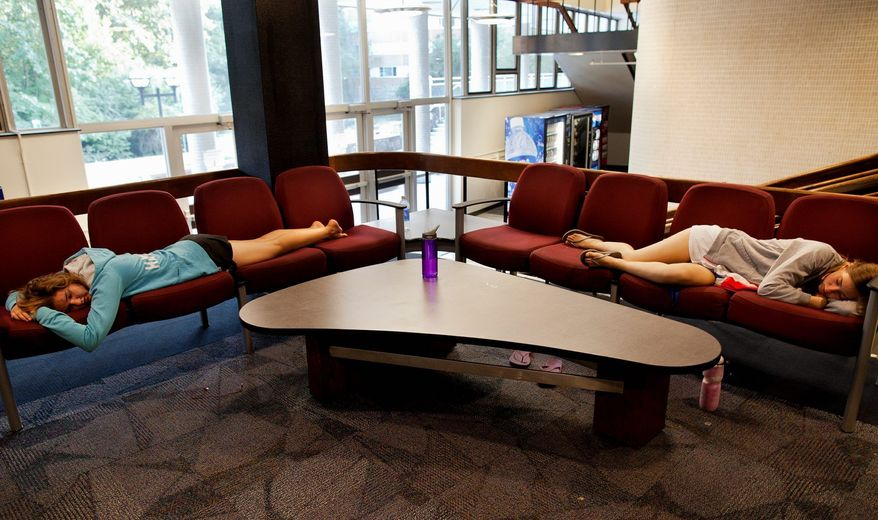 Michigan Science, Technology, Engineering and Mathematics Academy members Noelle Hansford (left) and Andrea Case take a nap in the lobby of Bursley Hall on the campus of the University of Michigan in Ann Arbor, Mich., recently. About three-quarters of all college students have indicated having occasional sleep problems. (Associated Press)