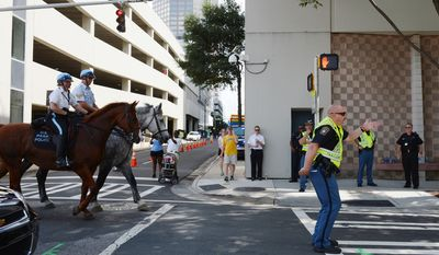 Mike Johnson, right, with the Layton County Sheriff's office directs traffic along Church Street in Charlotte, N.C. A day before the Democratic National Convention starts, many streets were closed off already. (Barbara L. Salisbury/The Washington Times)