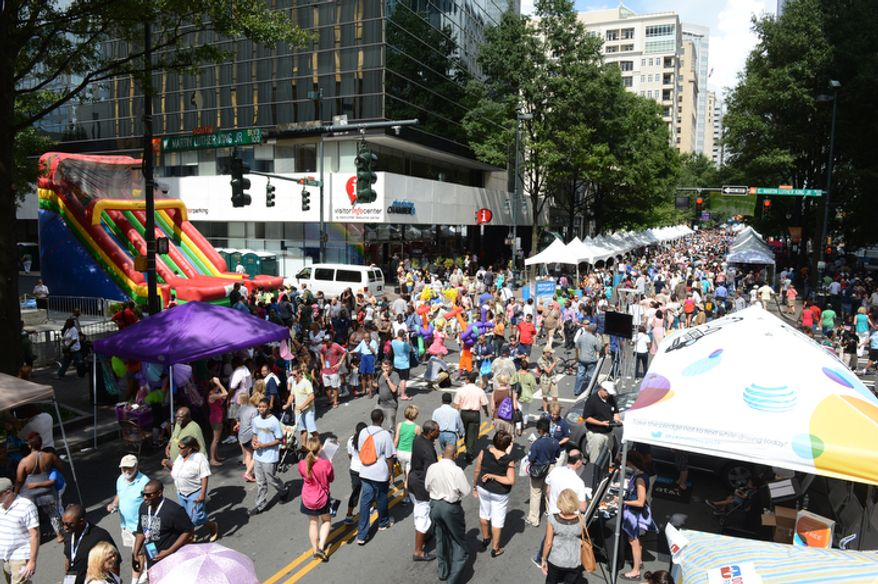 Hundreds of people walk up and down Tryon Street for the CarolinaFest in Charlotte, N.C. on Monday, Sept. 3, 2012. The day before the Democratic National Convention starts, the town hosted a street fair. (Barbara L. Salisbury/The Washington Times)