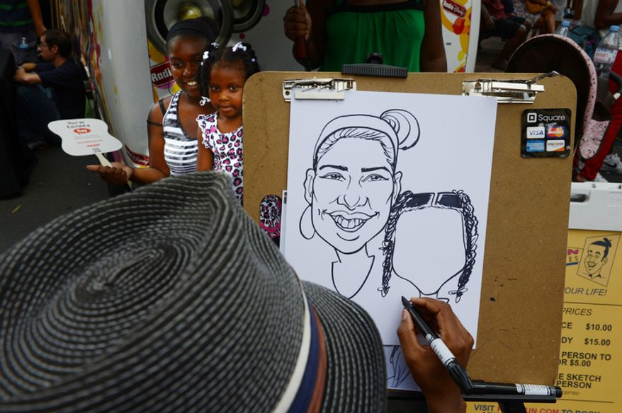 Two girls get a caricature drawn of them at CarolinaFest. (Barbara L. Salisbury/The Washington Times)