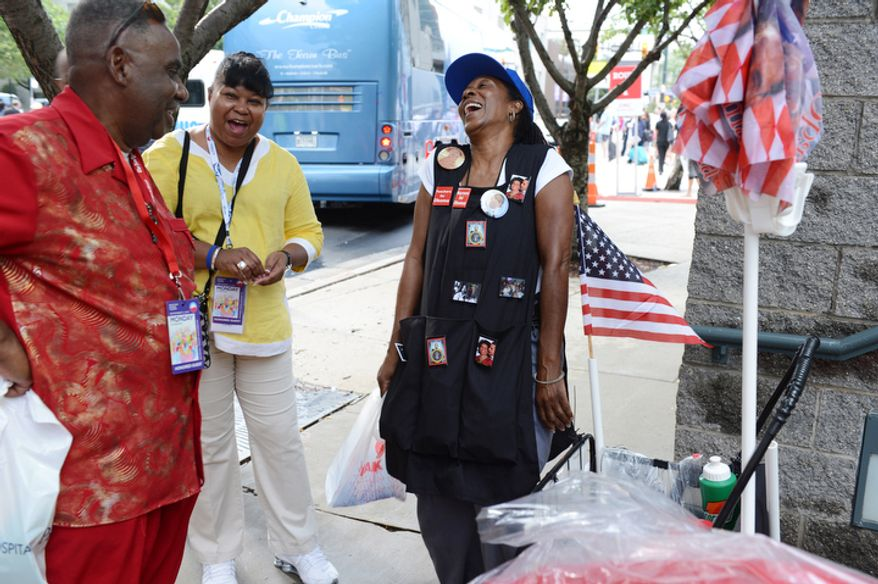 Claudia Blakemore, right, a registered nurse from Houston, Tex., laughs with Howard Foreman, left, from Vinton, La., and Audrey Cumby of LaMarque, Tex., outside the Charlotte Convention Center in Charlotte, N.C. Blakemore drove to the convention to sell Obama memorabilia, including hats, buttons and flags. She also sold things at the last DNC in 2008. (Barbara L. Salisbury/The Washington Times)