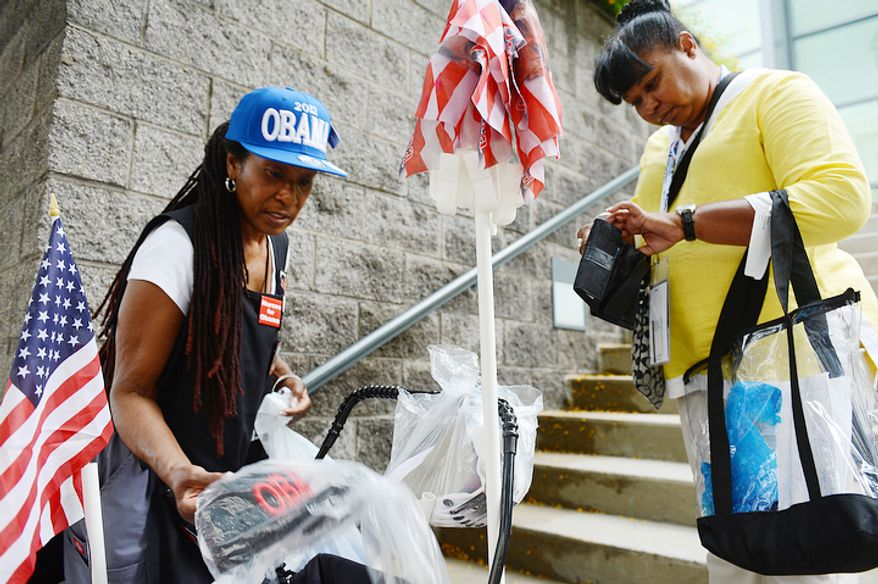 Claudia Blakemore, left, a registered nurse from Houston, Tex., sells an Obama hat to Audrey Cumby of LaMarque, Tex. outside the Convention Center in Charlotte, N.C. on Monday, Sept. 3, 2012. (Barbara L. Salisbury/The Washington Times)