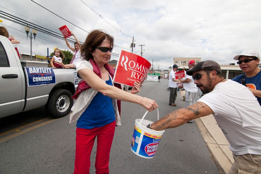 Romney campaign members pass out candy and fliers about the upcoming election.  (Craig Bisacre/The Washington Times)