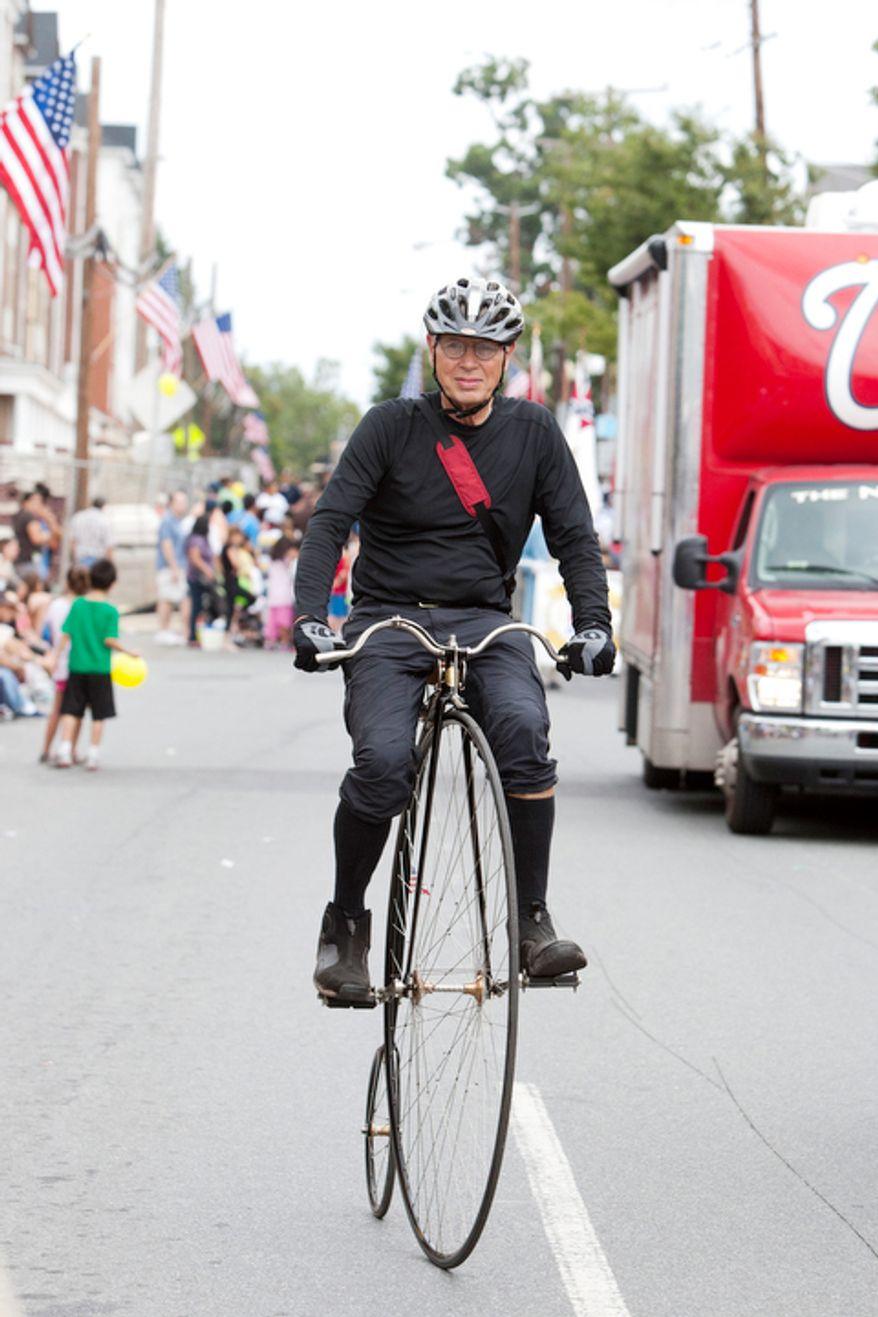 A high wheel bicycle rider peddles down E. Diamond Ave.  (Craig Bisacre/The Washington Times)
