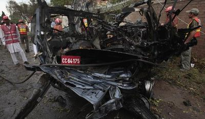 Pakistani officials and rescue workers gather at the site of the suicide bombing of a U.S. government vehicle in Peshawar, Pakistan, on Monday, Sept. 3, 2012. A (AP Photo/Mohammad Sajjad)