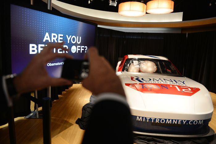 A spectator takes a photograph of the Romney campaign race car after Republican National Committee Chairman Reince Priebus and Rep. Jason Chaffetz, R-Utah, hold a press conference at the NASCAR Hall of Fame where the Republicans will respond to Democrat press conferences and other events at the Democratic National Convention in Charlotte, N.C., on Monday, September 3, 2012. (Barbara Salisbury/ The Washington Times)