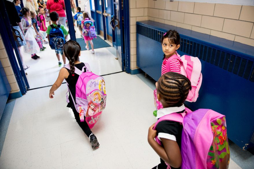Children make their way to class on the first day back to school at North Springfield Elementary School. (Andrew Harnik/The Washington Times)
