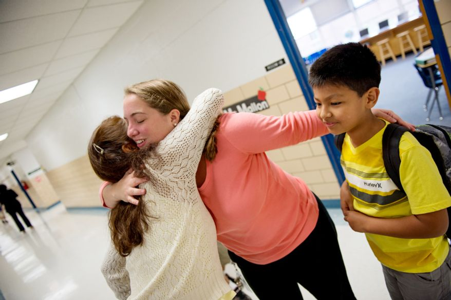 2nd grade teacher Ali Mallon hugs Brandon Romero's mother, on Brandon's first day back to school at North Springfield Elementary School. (Andrew Harnik/The Washington Times)