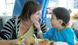 Ihor Lakatosh of Ukraine, who is 8 or 9 years old and weighs less than 30 pounds, interacts with his legal guardian, Anna Rishko, also of Ukraine, in his room at Shriners Hospital for Children in Boston. Ihor, who has burns on more than 30 percent of his body, was brought to Shriners through a nonprofit organization. (Associated Press)