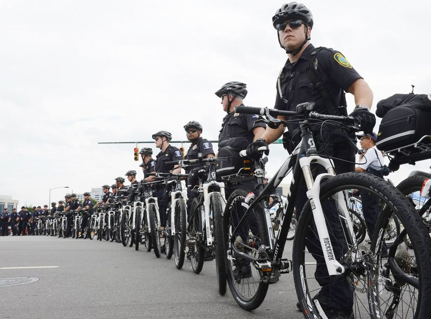 Police officers use their bicycles to create a perimeter to keep protesters inside a designated area along Stonewall Street in Charlotte, N.C. on Tuesday, Sept. 4, 2012. Protesters are allowed to march and demonstrate at the Democratic National Convention but are being kept well away from DNC venues. (Barbara L. Salisbury/The Washington Times)
