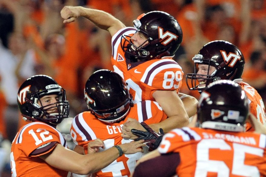 Virginia Tech place kicker Cody Journell (89) celebrates with Trey Gresh (12) and George George (48) after making a 17-yard field goal in overtime to win an NCAA college football game against Georgia Tech, Monday, Sept. 3, 2012, in Blacksburg, Va. Virginia Tech won 20-17. (AP Photo/Don Petersen)