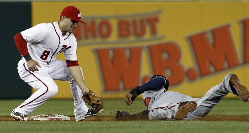 Washington Nationals second baseman Danny Espinosa makes the tag on Atlanta Braves' Jason Heyward, right, who was out at second on the steal attempt, during the sixth inning of a baseball game at Nationals Park on Tuesday, Aug. 21, 2012, in Washington. The Nationals won 4-1. (AP Photo/Alex Brandon)
