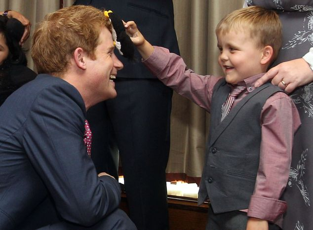 Britain's Prince Harry talks with Alex Logan (right), who puts a toy penguin against Harry's head, at the WellChild awards ceremony at the InterContinental Park Lane Hotel in London on Monday, Sept. 3, 2012. (AP Photo/Lewis Whyld)
