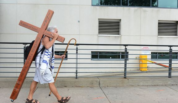 A man walks up Stonewall Street in Charlotte, N.C. on Tuesday, Sept. 4, 2012 carrying a cross. He said he is at the Democratic National Convention to remind people that what they are looking at is political and temporal, and that the true hope and change is Jesus Christ. (Barbara L. Salisbury/The Washington Times)