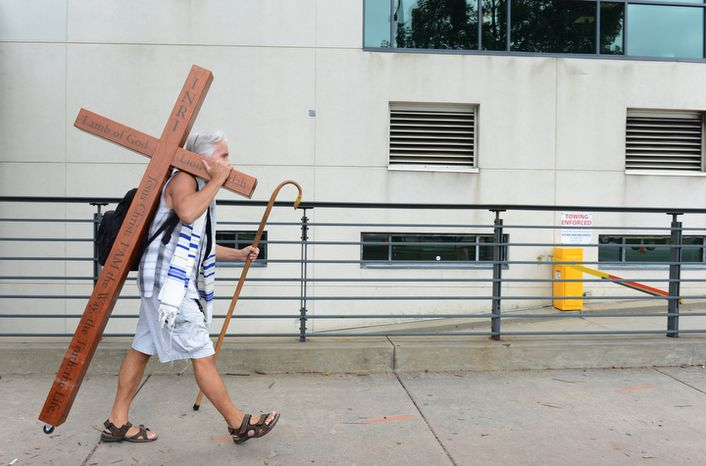 Ken Yarmosh,  of Charlotte, N.C. walks up Stonewall Street in Charlotte, N.C. on Tuesday, Sept. 4, 2012 carrying a cross. He said he is at the Democratic National Convention to remind people that what they are looking at is political and temporal, and that the true hope and change is Jesus Christ. (Barbara L. Salisbury/The Washington Times)