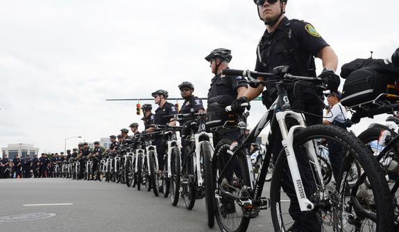 Police officers use their bicycles to create a perimeter to keep protesters inside a designated area along Stonewall Street in Charlotte, N.C. Protesters are allowed to march and demonstrate at the Democratic National Convention but are being kept well away from DNC venues. (Barbara L. Salisbury/The Washington Times)