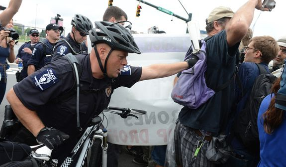 A police officer pushes a protester back into the protest zone created by police in the streets of Charlotte outside the Democratic National Convention. (Barbara L. Salisbury/The Washington Times)