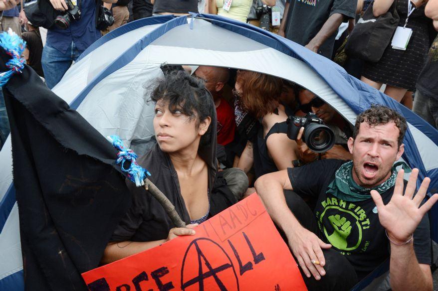 "Protesters pull out a tent and cram 13 people inside of it, chanting, ""This is affordable housing!"" and then, ""Out of the tents and into the streets!"" in Charlotte, N.C. There are hundreds of Occupy protesters in town for the Democratic National Convention. (Barbara L. Salisbury/The Washington Times)"