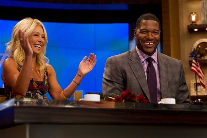 """Former football player Michael Strahan, right, sits with Kelly Ripa on the set of the newly named """"Live! with Kelly and Michael"""" on Tuesday, Sept. 4, 2012 in New York. Strahan joined the popular morning show as a permanent co-host on Tuesday, fulfilling a joking prophecy he made to Regis Philbin more than four years ago. (Photo by Charles Sykes/Invision/AP Images)"""