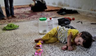 A Syrian child who fled her home in Aleppo with her family because of fighting between the rebels and the Syrian army, rests Wednesday at a school where she and her family took refuge, in Suran, Syria. (Associated Press)
