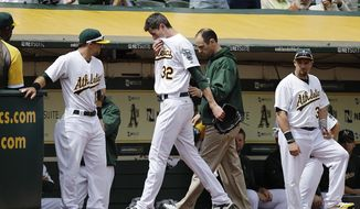 Oakland Athletics pitcher Brandon McCarthy (32) leaves the field with a trainer after being hit in the head by a ball hit by Los Angeles Angels' Erick Aybar in the fourth inning of a baseball game, Wednesday, Sept. 5, 2012, in Oakland, Calif. (AP Photo/Ben Margot)