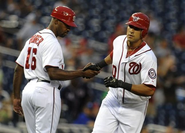 Washington Nationals' Ian Desmond, right, receives congratulations from his third base coach Bo Porter after hitting a two-run home run in the first inning of their baseball game against the Chicago Cubs at Nationals Park, Tuesday, Sept. 4, 2012, in Washington. (AP Photo/Richard Lipski)